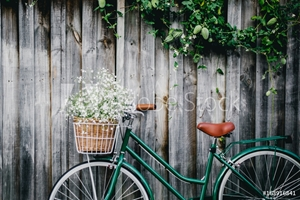 Bild på Bicycle against wooden fence with flowers in basket