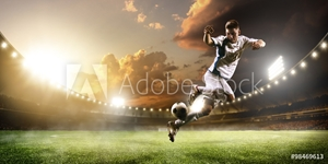 Bild på Soccer player in action on sunset stadium panorama background